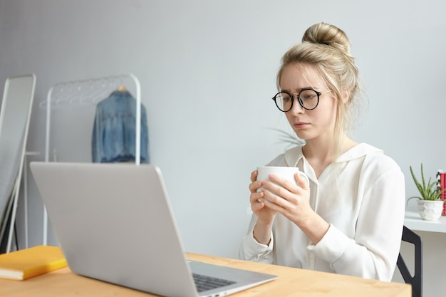 Deadline and overwork concept. frustrated young caucasian female freelancer in stylish eyewear drinking another cup of coffee while working on urgent project, sitting in front of open laptop