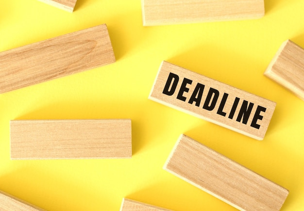 Deadline text written on a wooden blocks on a yellow background. business concept