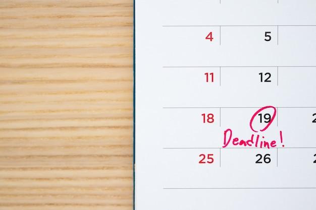 白いカレンダーページの日付の締め切り書き込みクローズアップ