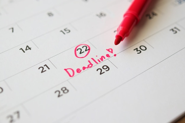 Deadline write on white calendar page date close up