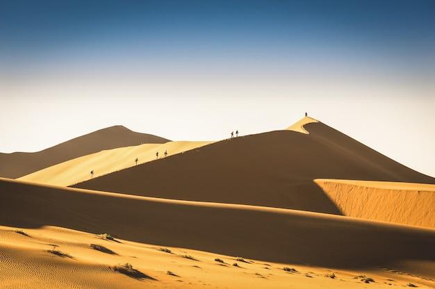 Туристические люди путешественники, путешествующие пешком по песчаной дюне в deadvlei около sossusvlei в намибии