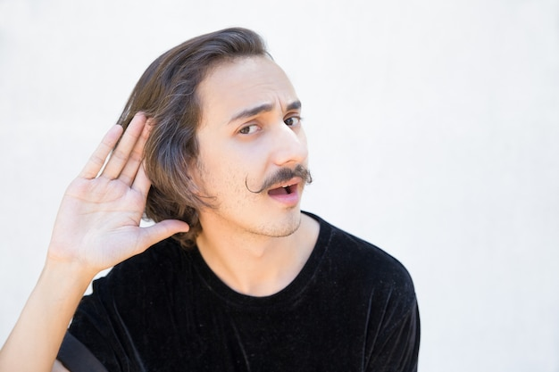Deaf man with mustache cupping hand behind ear.