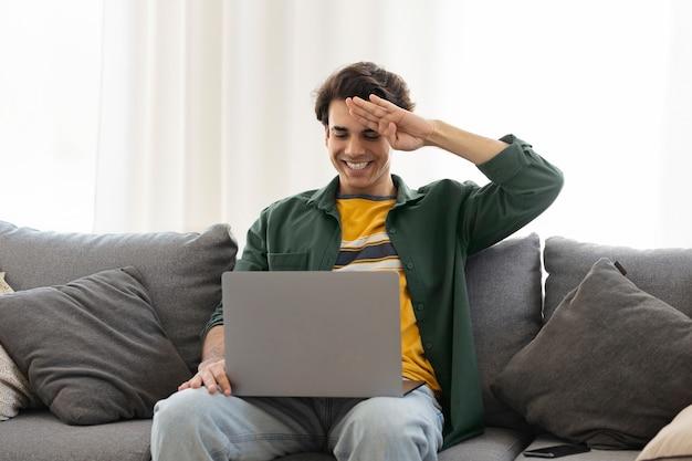 Глухой или слабослышащий счастливый улыбающийся молодой кавказец использует язык жестов во время видеозвонка с помощью ноутбука, сидя на диване у себя дома