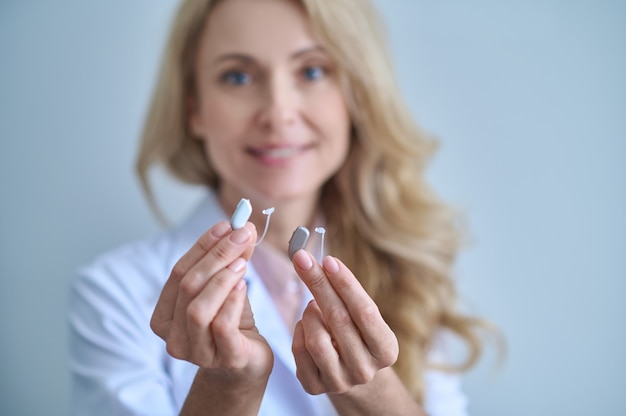 Deafness help. two different hearing aids in outstretched hands of smiling pretty woman in medical gown on light background