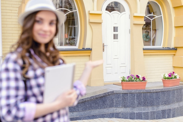 Deal contract people person shop store concept. close up portrait of pretty professional seller demonstrating gesturing with hand  white door of new yellow house looking in camera holding tablet