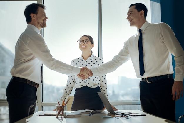 Сделка оговаривается. оптимистичные успешные бизнесмены пожимают друг другу руки, обязывая сделку, в то время как их коллега лучезарно улыбается им