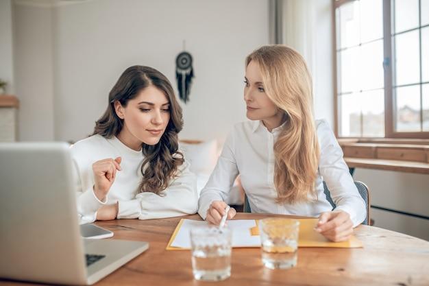 거래 조건. 테이블에 앉아 거래 조건을 논의하는 두 여성