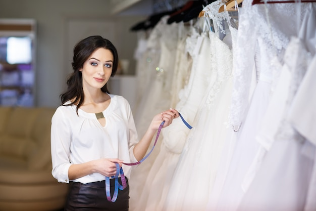 Dealer consultant in the background of wedding dresses