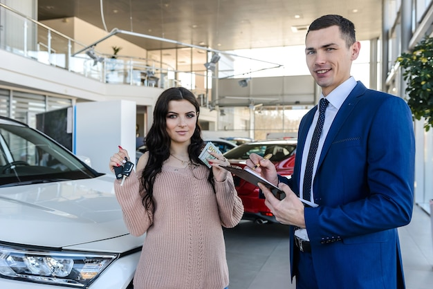 Dealer giving keys from new car to beautiful woman