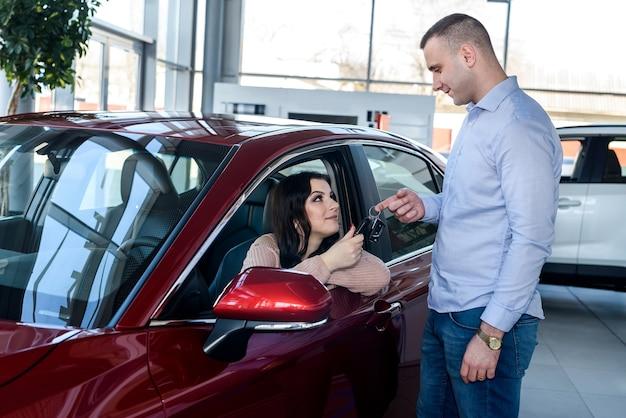 새 차에서 아름다운 여인에게 열쇠를주는 딜러