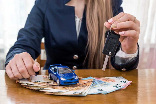 Dealer holding keys from car, toy car and euro money
