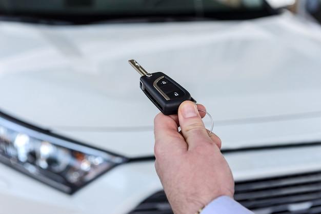 새 차에서 키를 들고 딜러를 닫습니다.