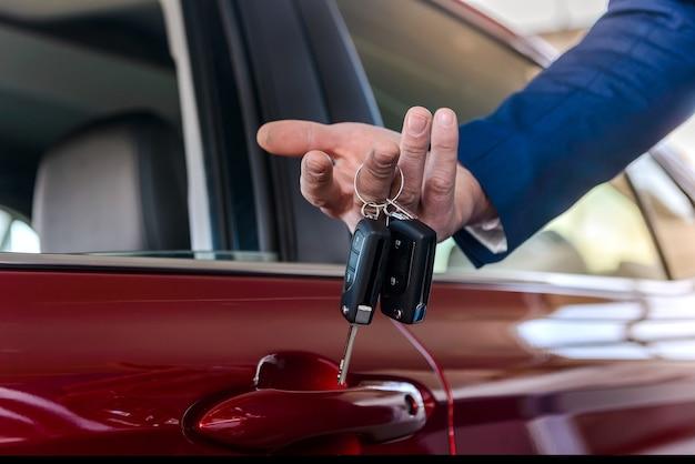 Dealer holding keys from new car close up