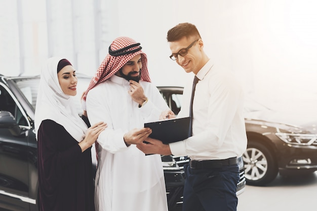 Dealer sells car rich arab client reads contract.