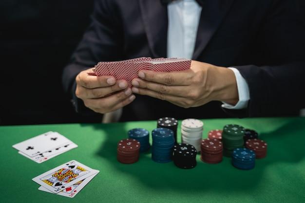 딜러가 카지노에서 포커 카드를 섞습니다.