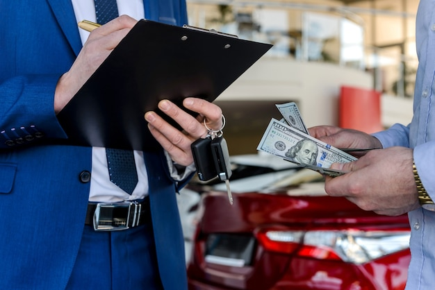 Dealer signing contract and buyer counting money, close up