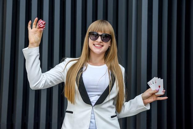 포커 칩과 추상적 인 배경에 카드 놀이 딜러. 카메라를 위해 포즈를 취하는 카지노 칩을 들고 선글라스에 여자