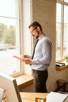 거래. 사무실에서 일하고 젊은 사업가 새로운 작업 장소를 점점. 승진 후 관리하는 동안 젊은 남성 회사원. 진지하고 자신감있는 것 같습니다. 비즈니스, 라이프 스타일, 새로운 생활 개념.