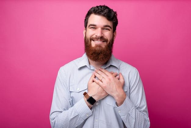 親愛なる私の心。ひげを生やした男はピンクの背景にカメラを見て素敵に彼の心に手を握ります。