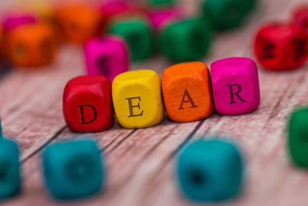 Dear - word created with colored wooden cubes on desk.