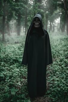 Смерть в черной толстовке с капюшоном в лесу
