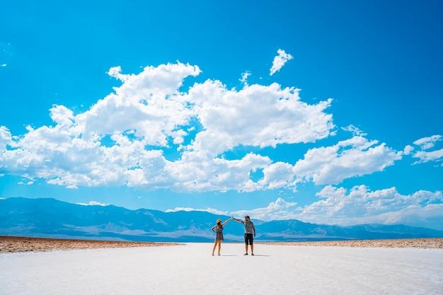 Долина смерти, калифорния, сша. пара туристов бьются руками о белую соль в бассейне бадуотер.