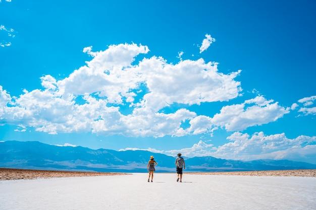 Долина смерти, калифорния, сша. пара туристов, гуляющих по белой соленой равнине бассейна бэдуотер.