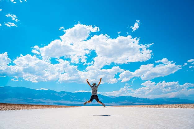 Долина смерти, калифорния, сша. молодой человек прыгает на спине на белой соли бассейна бэдуотер