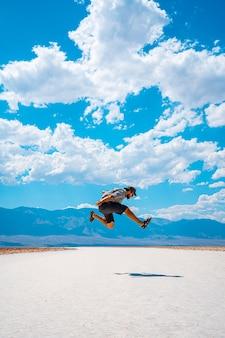 Долина смерти, калифорния, сша. молодой человек прыгает в синей рубашке по белой соли бассейна бэдуотер.