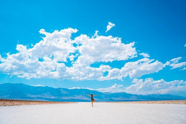 デスバレー、カリフォルニア州アメリカ合衆国。バッドウォーター盆地の白い塩のフラットでヨガを練習する若い女性