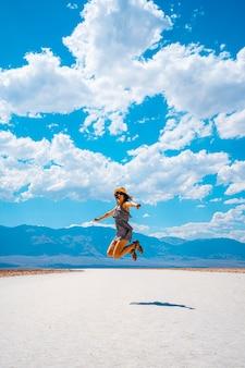 데스 밸리, 캘리포니아 미국. 배드 워터 분지의 하얀 소금에 파란색 셔츠와 함께 점프하는 젊은 여성