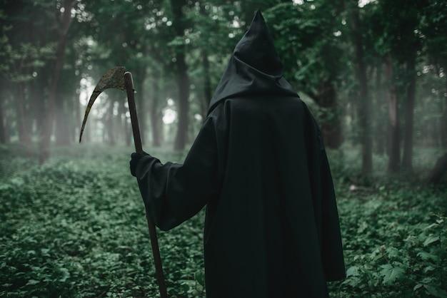 Смерть с косой в темном туманном лесу