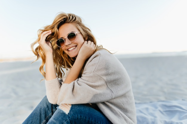 Debinair blinde woman sitting at sandy beach in autumn morning. outdoor portrait of pretty curly woman smiling in the sea