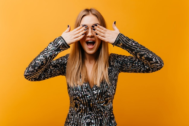 Debinair white woman with trendy manicure covering her eyes. indoor portrait of laughing excited woman standing on orange.