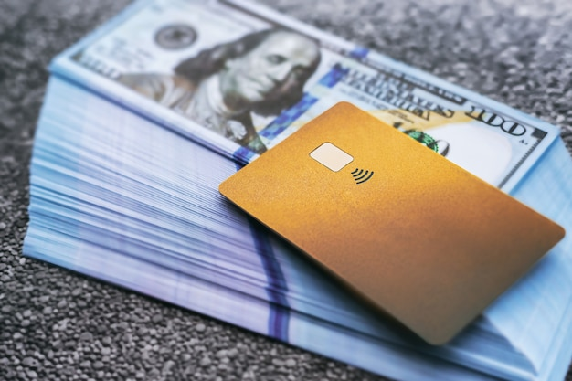 デビットプラスチックカードは米ドルの山に横たわっています、トピックは金融と貸付、クローズアップです