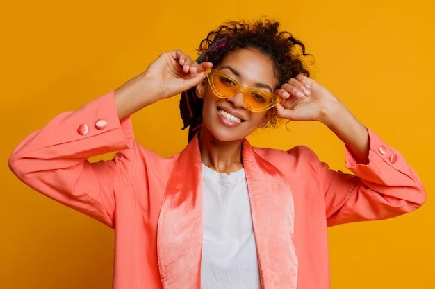 完璧な笑顔、巻き毛、自然なデボネアアフリカ女性は、スタジオで黄色の背景にピンクのトレンディなジャケットでポーズをとります。
