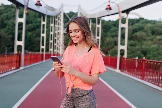 トレーニング中に電話を使用してデボネアブロンドの女性。朝のスタジアムでポーズをとってカジュアルな服装で笑顔の女の子。