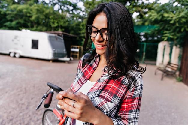 Debonair 갈색 머리 여자 문자 메시지 거리에. 행복 한 미소로 전화 화면을보고 세련 된 셔츠에 좋은 유머 소녀.