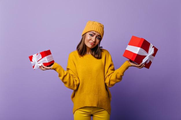 Debonair 백인 여자 생일을 들고 슬픈 미소로 presnets. 보라색에 노란색 니트 복장 서에서 사랑스러운 젊은 여자의 실내 초상화.