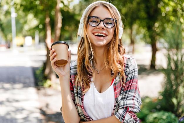 Debonair кавказская дама выражает положительные эмоции в парке. наружное фото улыбающейся великолепной женщины, пьющей кофе на природе.