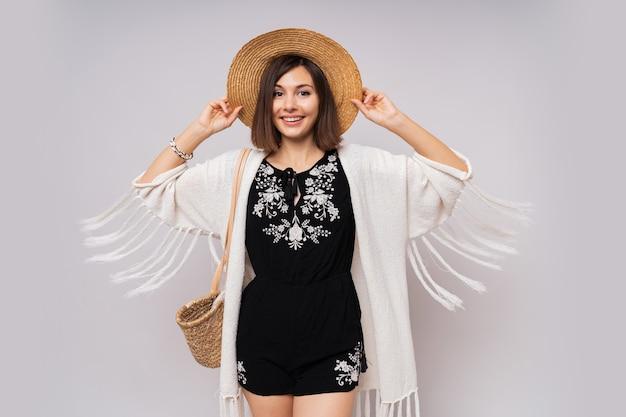 Жизнерадостная темноглазая девушка в соломенной шляпе и летнем наряде в стиле бохо позирует.