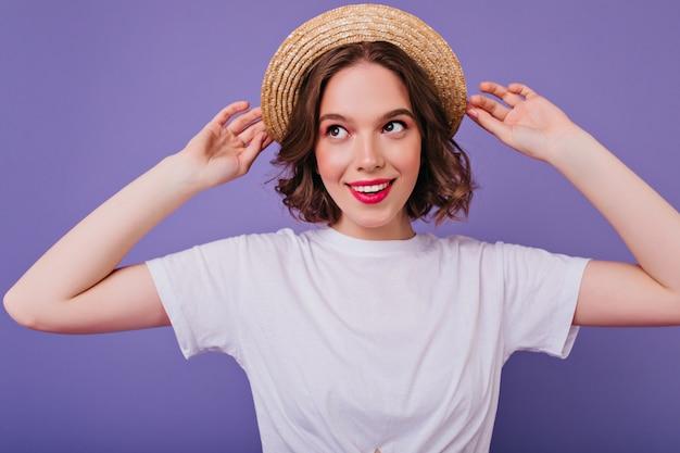紫色の壁に笑顔でポーズをとる白いtシャツのデボネア暗い目の女の子。麦わら帽子に触れている熱狂的な白人女性の屋内写真。