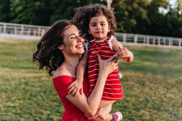 Debonair donna europea godendo la mattina del fine settimana con la piccola figlia. splendida giovane mamma in posa nel parco con il bambino riccio.
