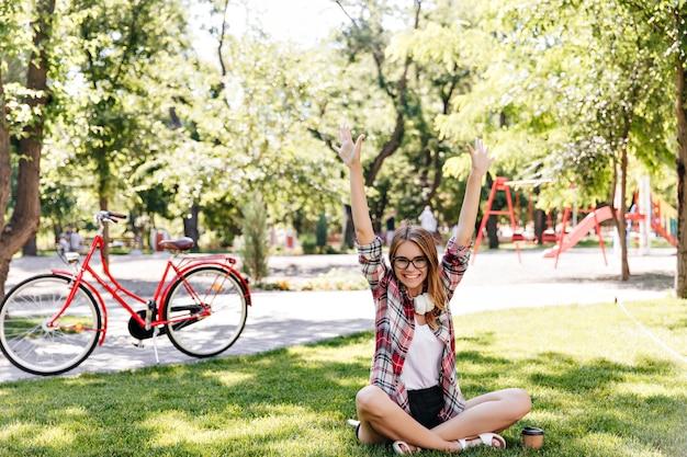 公園で良い春の日を楽しんでいるデボネアの女性モデル。緑の草の上に座っているウェーブのかかった髪の熱狂的な女の子。