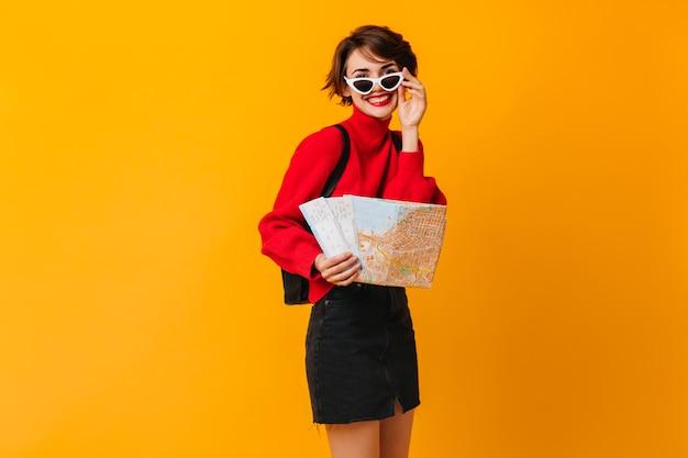 Turista femminile debonair toccando occhiali da sole sulla parete gialla
