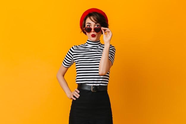 Debonair french woman wearing heart-shaped sunglasses