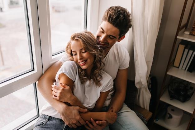 彼氏と週末を楽しんでいるデボネアの女の子。一緒に朝を過ごす笑っているカップルの屋内の肖像画。