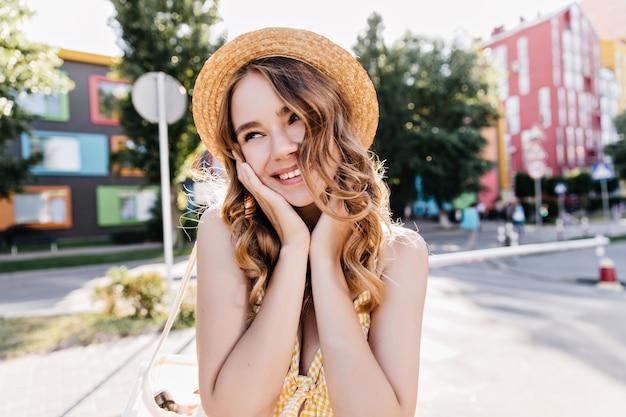 晴れた日にふざけて見回す麦わら帽子のデボネアの女の子。恥ずかしがり屋の笑顔でポーズをとって嬉しい金髪の女性の屋外の肖像画。