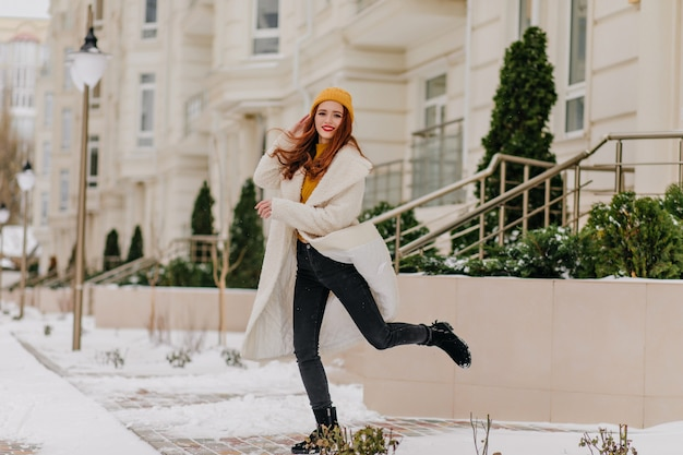Девушка debonair в белом халате прыгает в зимний день. наружное фото мечтательной женщины, наслаждающейся холодной погодой.