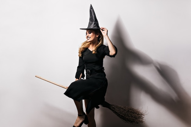 Девушка debonair в костюме ведьмы, наслаждаясь карнавалом. фото мечтательной светловолосой дамы, весело проводящей время в хэллоуин.